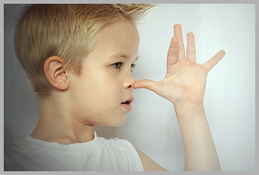 Little boy touching nose with thumb