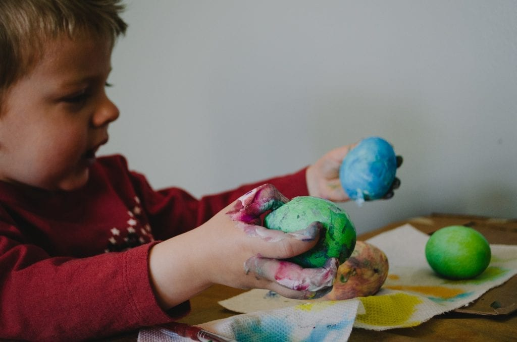 Little boy painting eggs